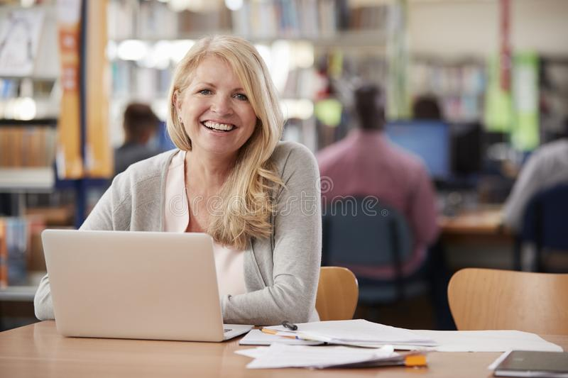 Portrait Of Mature Female Student Using Laptop In Library royalty free stock image