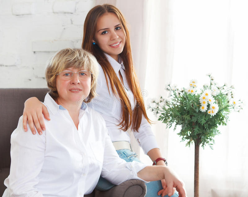 Portrait of a mature grandmother and teen granddaughter and teen royalty free stock image