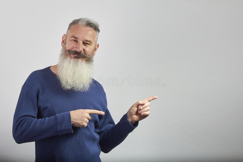 Portrait of mature gray-haired bearded man in blue sweatshirt points forefingers to side on gray background, selective focus. Portrait of mature gray-haired stock photo