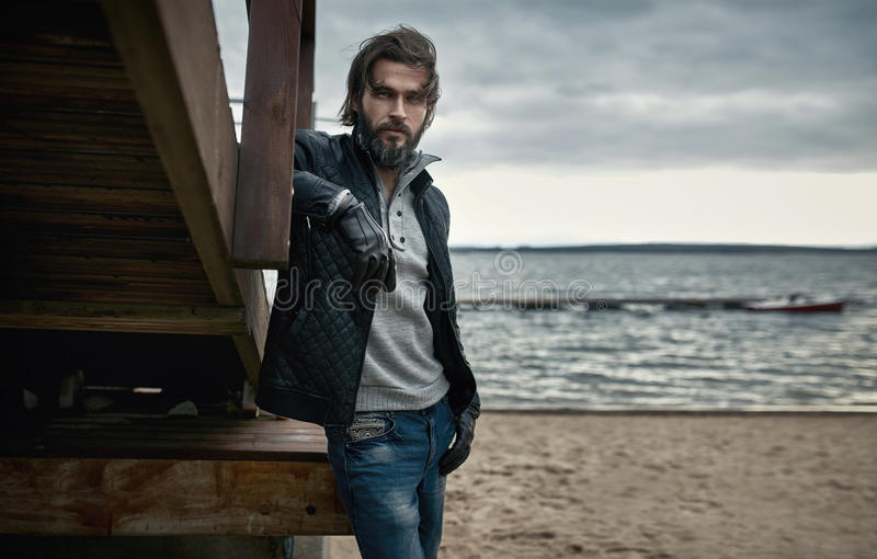 Portrait of a mature handsome guy resting on the autumn beach royalty free stock photos