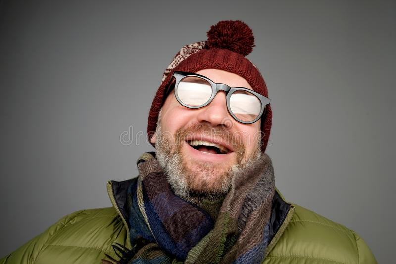 Portrait of mature hipster man in glasses and hat posing. Smiling bearded man wearing warm clothes for winter stock photos