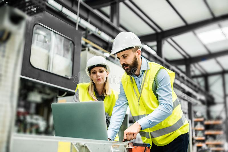 A portrait of an industrial man and woman engineer with laptop in a factory, working. A portrait of a mature industrial men and women engineer with laptop in a stock image