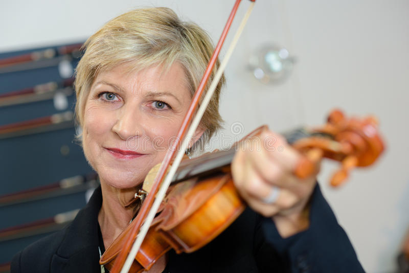 Portrait mature lady playing violin stock photo