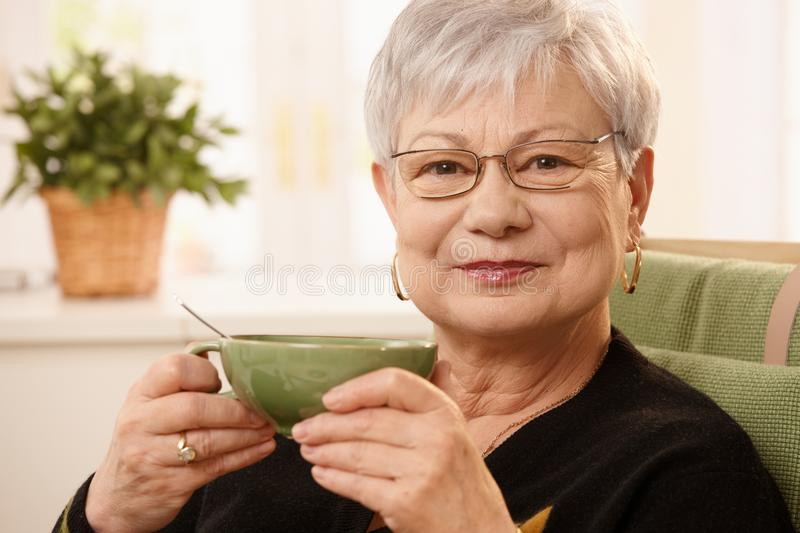 Portrait of mature lady with teacup. Closeup portrait of mature lady sitting at home holding teacup, looking at camera royalty free stock photos