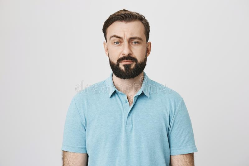 Portrait of a mature man with a beard and moustache looking suspicious. Person lifts his eyebrow and do not really stock image