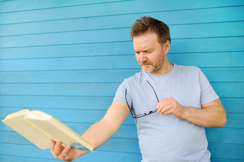 Portrait of mature man with big black eye glasses trying to read book but having difficulties seeing text because of vision stock photo