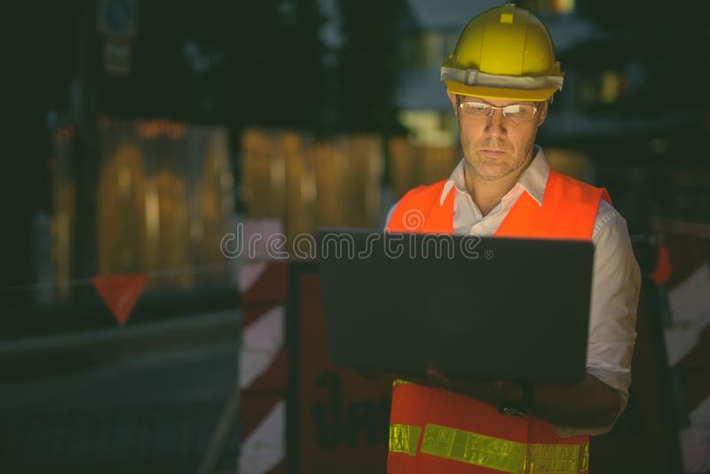 Mature man construction worker at the construction site in the city at night. Portrait of mature man construction worker at the construction site in the city at royalty free stock images