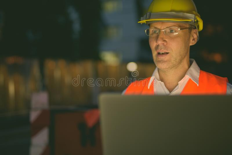 Mature man construction worker at the construction site in the city at night stock photography