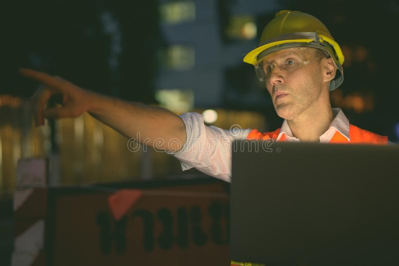 Mature man construction worker at the construction site in the city at night stock photos