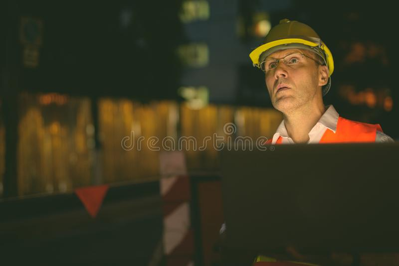 Mature man construction worker at the construction site in the city at night royalty free stock photos