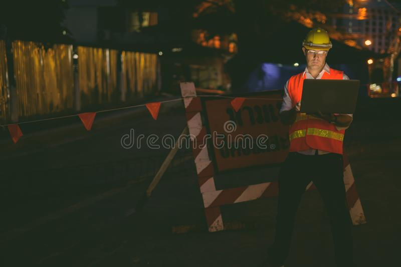 Mature man construction worker at the construction site in the city at night royalty free stock photo