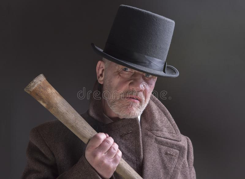 Sinister Victorian criminal holding a wooden bat. Portrait of a mature man dressed as a sinister Victorian criminal holding a wooden bat royalty free stock images