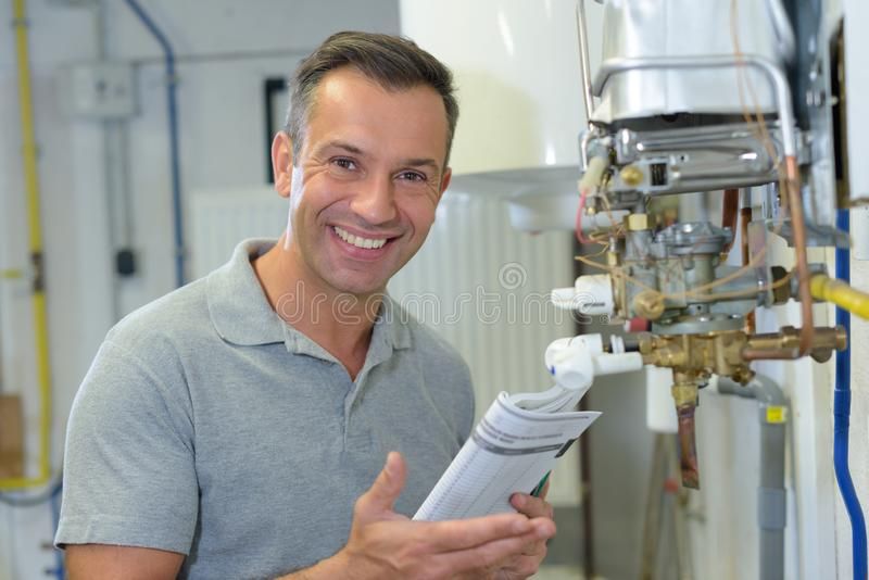 Portrait mature man holding instructions for gas boiler royalty free stock images