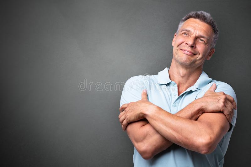 Portrait Of A Mature Man Hugging Himself stock photography