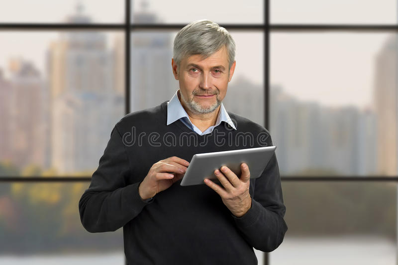 Portrait of mature man with pc tablet. stock photo