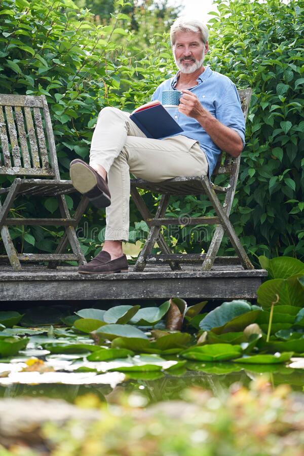 Portrait Of Mature Man Relaxing In Garden Reading Book On Jetty By Lake royalty free stock image
