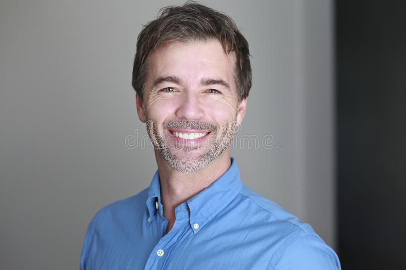 Portrait of a mature man smiling at the camera sitting royalty free stock image