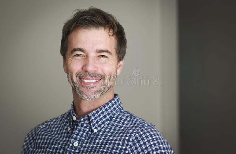 Portrait of a mature man smiling at the camera sitting stock images