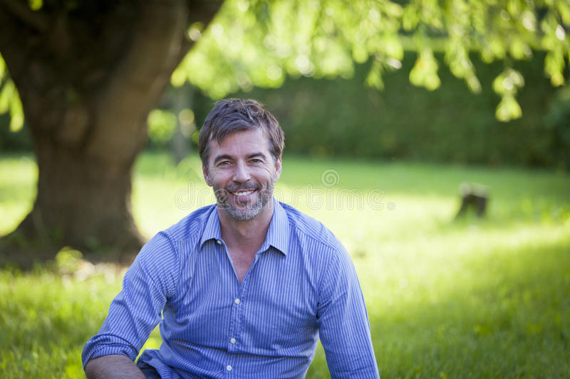 Portrait Of A Mature Man Smiling at the Camera sitting stock image