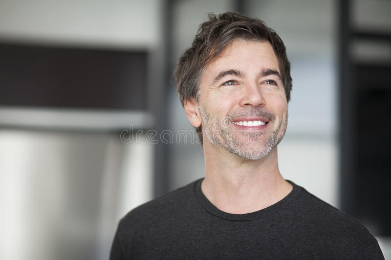 Portrait Of A Mature Man Smiling And looking away. stock images