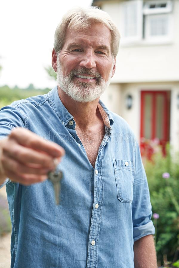 Portrait Of Mature Man Standing In Garden In Front Of Dream Home In Countryside Holding Keys. Portrait Of Mature Man Standing In Garden In Front Of Home In stock photo