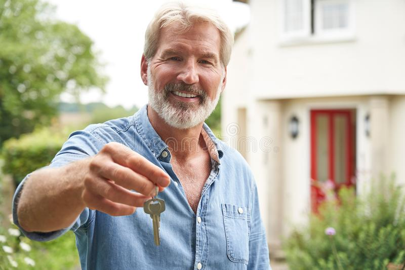 Portrait Of Mature Man Standing In Garden In Front Of Dream Home In Countryside Holding Keys. Mature Man Standing In Garden In Front Of Dream Home In Countryside royalty free stock photos