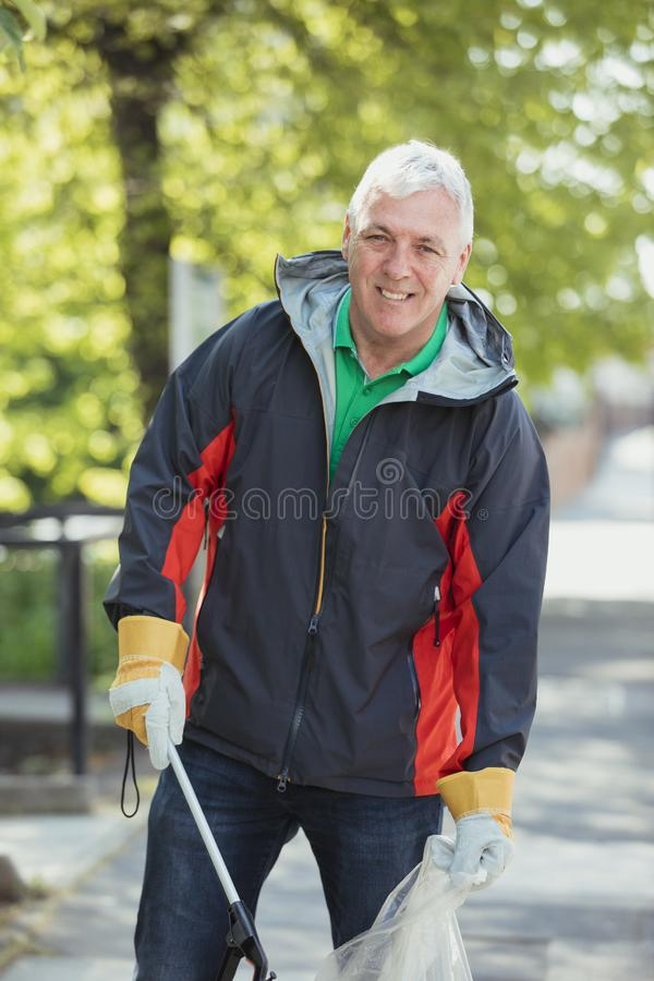 Portrait of a Male City Cleaner. A portrait of a mature man standing in a park, participating in a city clean up royalty free stock photography