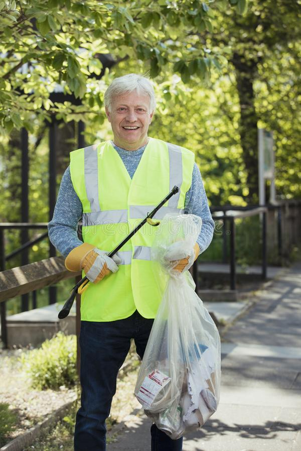 Mature Man City Cleaning. A portrait of a mature man standing in a park, wearing. a high visibility jacket and participating in a city clean up royalty free stock photo