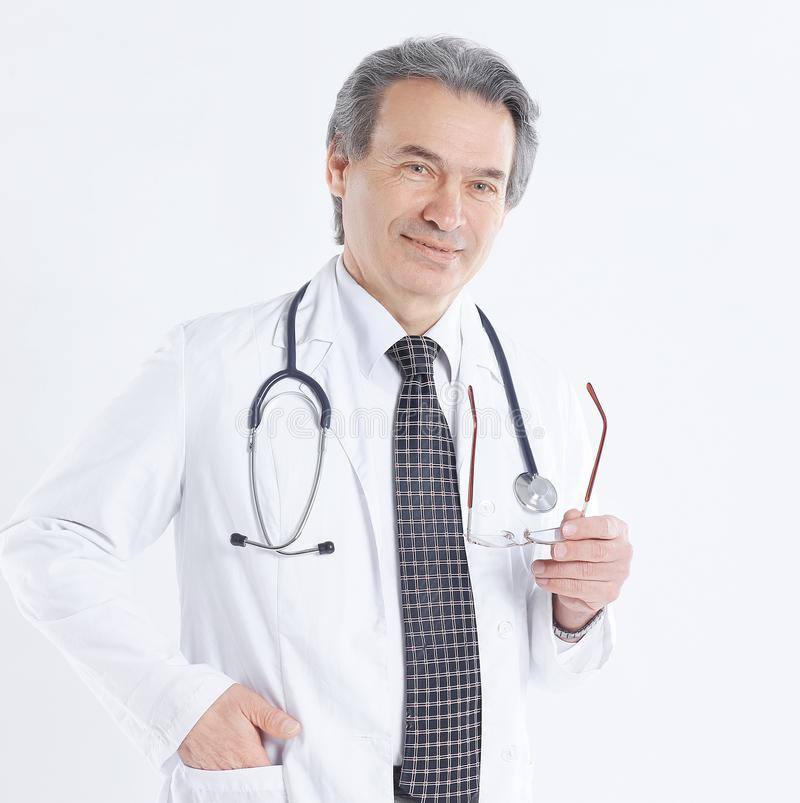 Portrait of mature medical doctor with white coat and stethoscope on isolated background.  stock photos