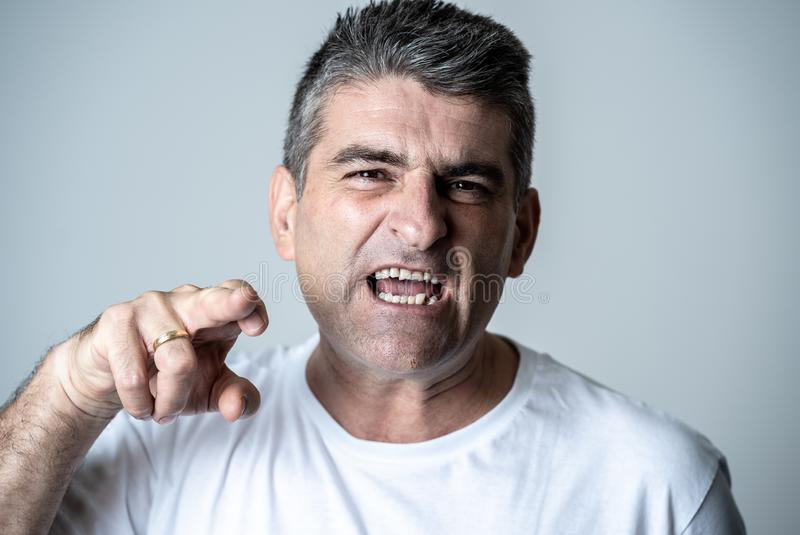 Portrait of a mature 40s to 50s white angry and upset man looking furious and aggressive human emotions facial expressions and royalty free stock photo
