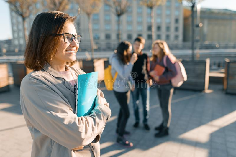Portrait of mature smiling female teacher in glasses with clipboard, outdor with a group of teenagers students, golden hour royalty free stock photography
