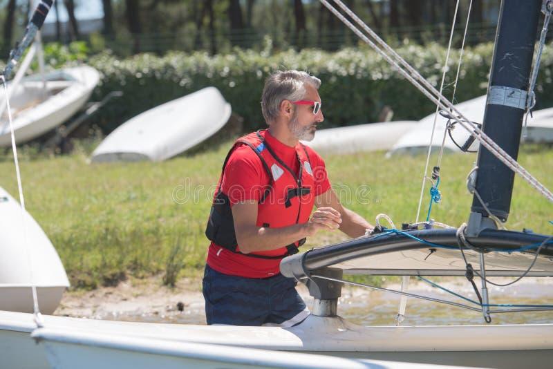 Portrait mature sportsman near catamaran royalty free stock photography
