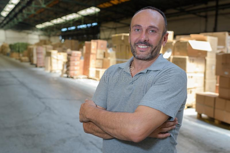 Portrait mature storeman in vast warehouse stock images