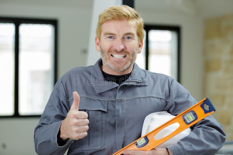 Portrait mature tradesman holding spirit level stock photo