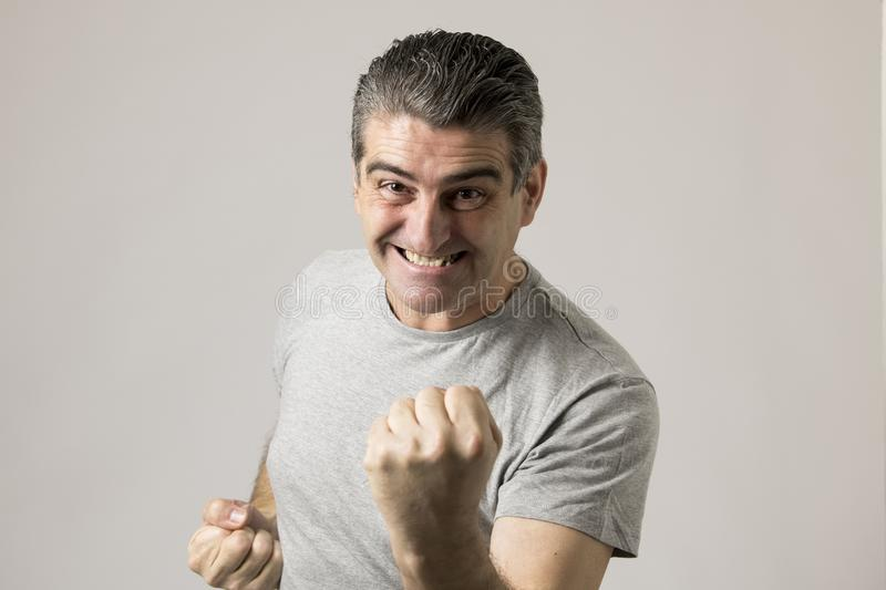 Portrait of mature white man 40 to 50 years old gesturing excited and happy with hands in victory and winner sign isolated on grey royalty free stock photos