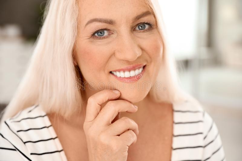 Portrait of mature woman with beautiful face on blurred background royalty free stock photography