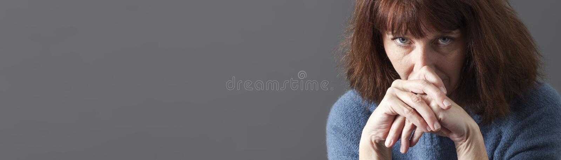 Upset beautiful 50s woman looking sad, gray copy space banner stock photos
