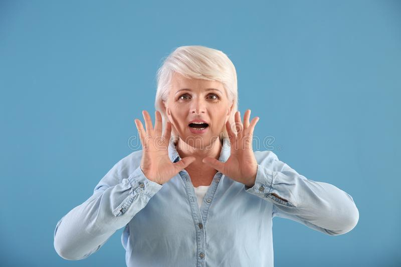 Portrait of mature woman calling for someone on color background stock photo