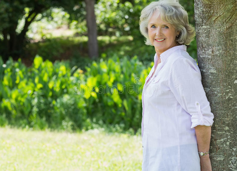 Portrait of mature woman leaning against tree trunk in park royalty free stock photography