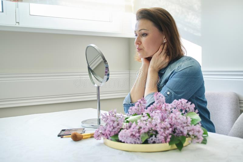 Portrait of mature woman with make-up mirror massaging her face and neck, beautiful female 40 years old royalty free stock images