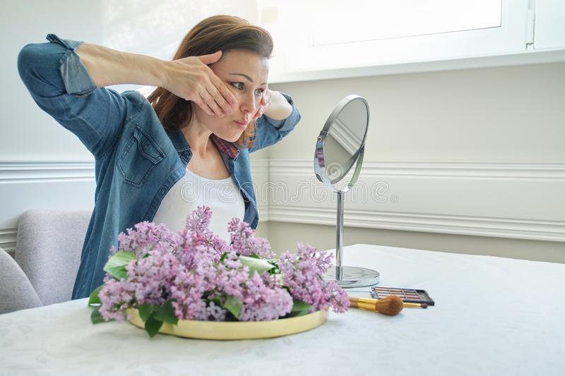 Portrait of mature woman with make-up mirror massaging her face and neck, beautiful female 40 years old stock photo
