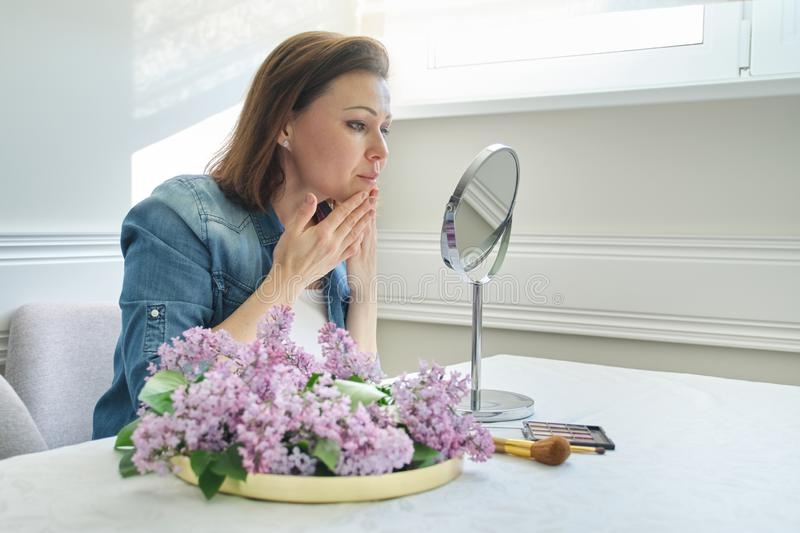 Portrait of mature woman with make-up mirror massaging her face and neck, beautiful female 40 years old royalty free stock photos