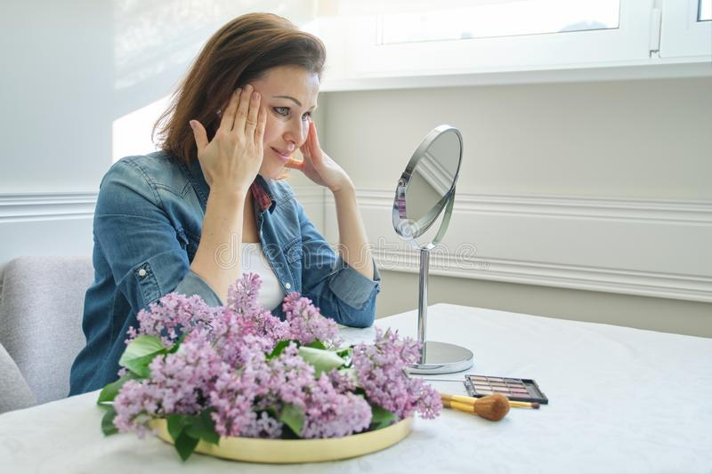 Portrait of mature woman with make-up mirror massaging her face and neck, beautiful female 40 years old royalty free stock photo