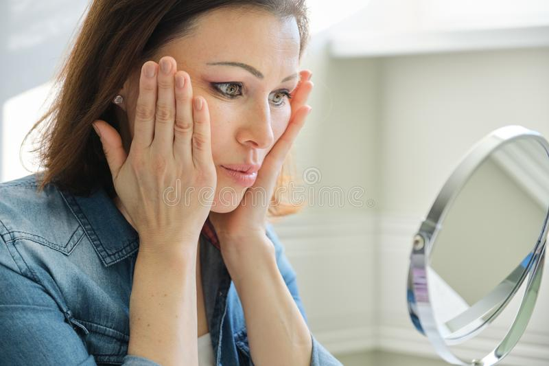 Portrait of mature woman with make-up mirror massaging her face royalty free stock images