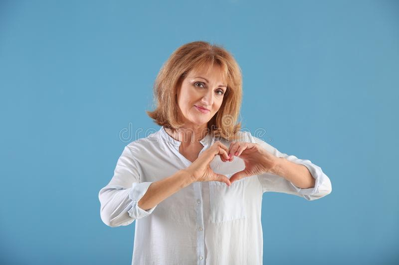 Portrait of mature woman making heart with her hands on color background royalty free stock photo