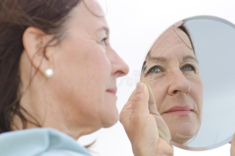 Portrait mature woman in mirror stock photography