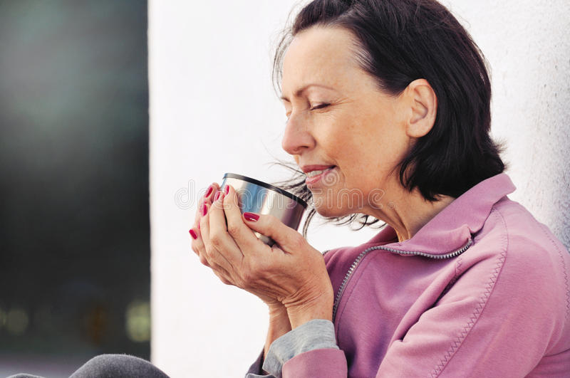 Portrait of mature woman resting after jog in the park with cup of hot tea royalty free stock image