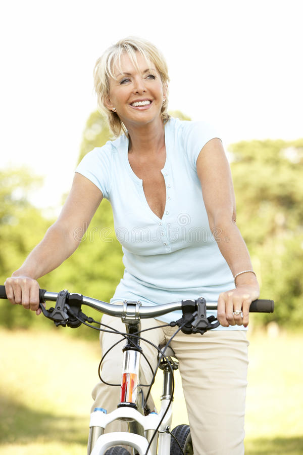 Portrait of mature woman riding cycle in countrysi royalty free stock photography