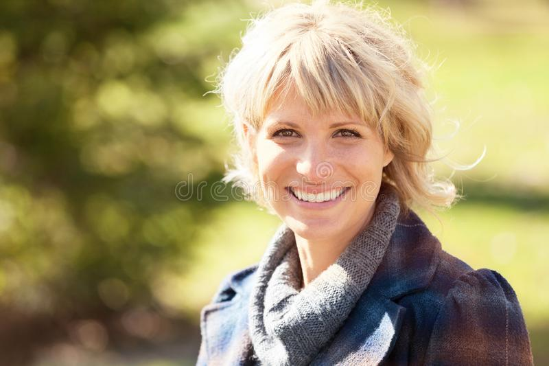 Portrait Of A Mature Woman Smiling At The Camera. She is really Happy in summertime stock photography