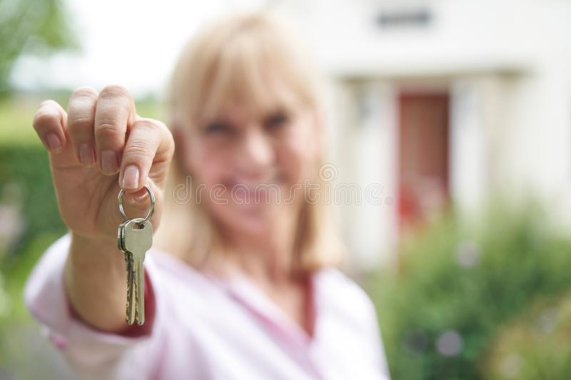 Portrait Of Mature Woman Standing In Garden In Front Of Dream Home In Countryside Holding Keys. Portrait Of Mature Woman Standing In Garden In Front Of Home In royalty free stock image